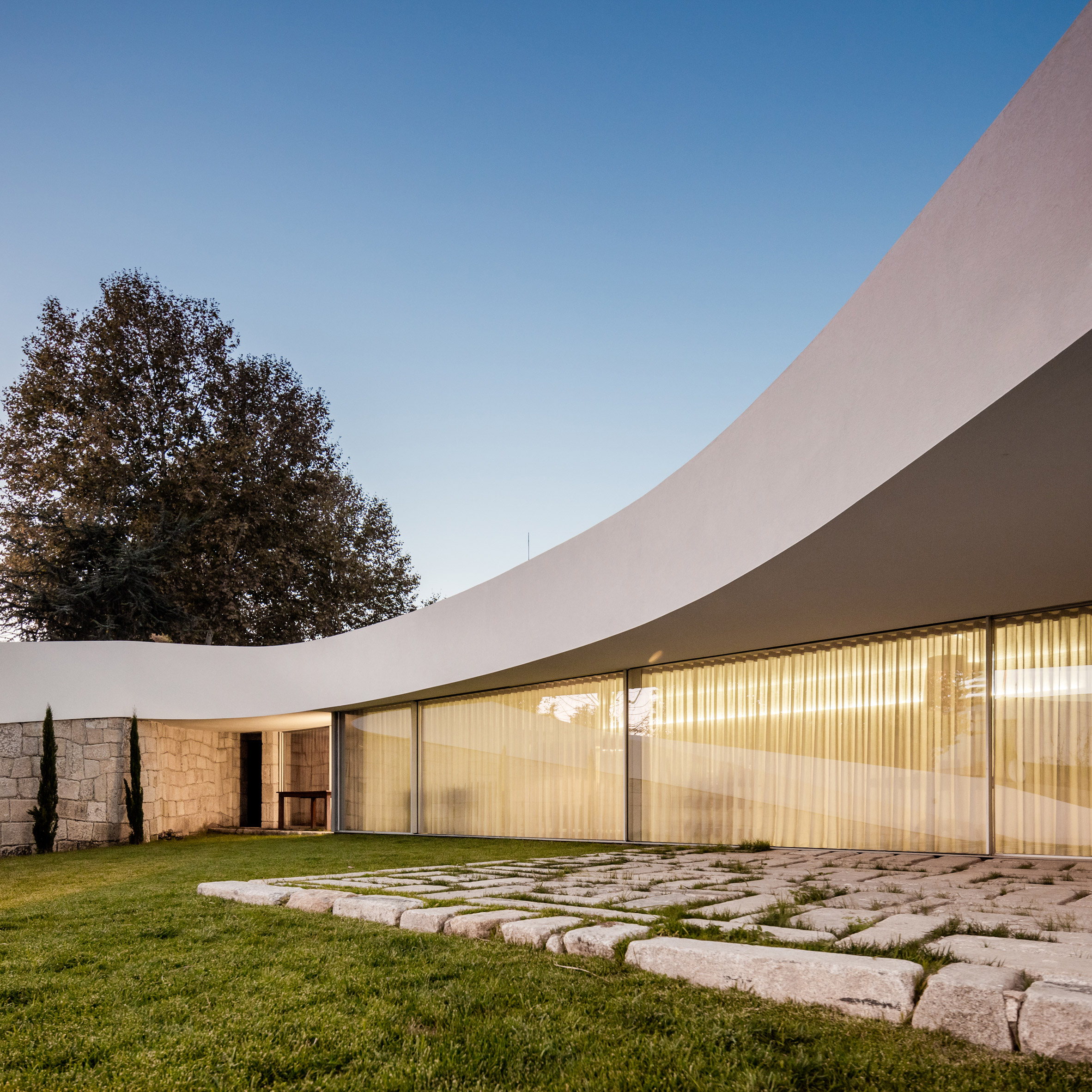 Curving Roof And Stone Walls Create Seclusion For Portuguese House By NOARQ