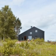 Asymmetric house clad in blackened pine stands in a Polish forest