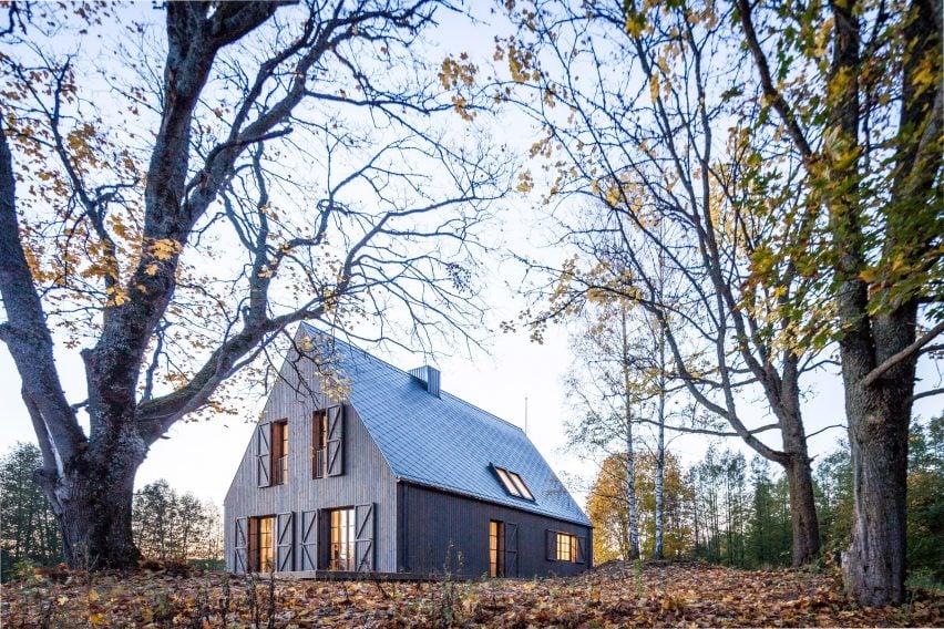Aketuri Architektai conceals windows and doors behind large timber shutters at Lithuanian lakeside retreat