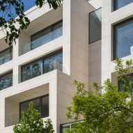 Stone-clad apartment building in Bucharest features recessed windows and terraces