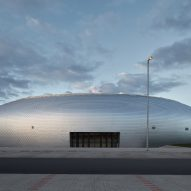 Domed sports hall by Sporadical is covered in scale-like aluminium shingles