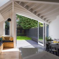 Angular doors connect tapered extension with tiled patio by Mustard Architects
