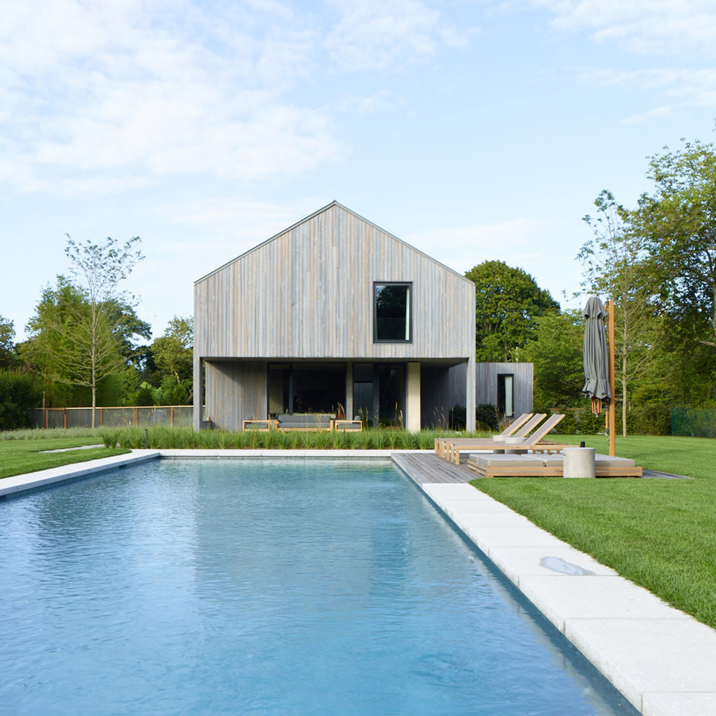 MB Architecture covers Hamptons farmhouse in charred cyprus inside and out