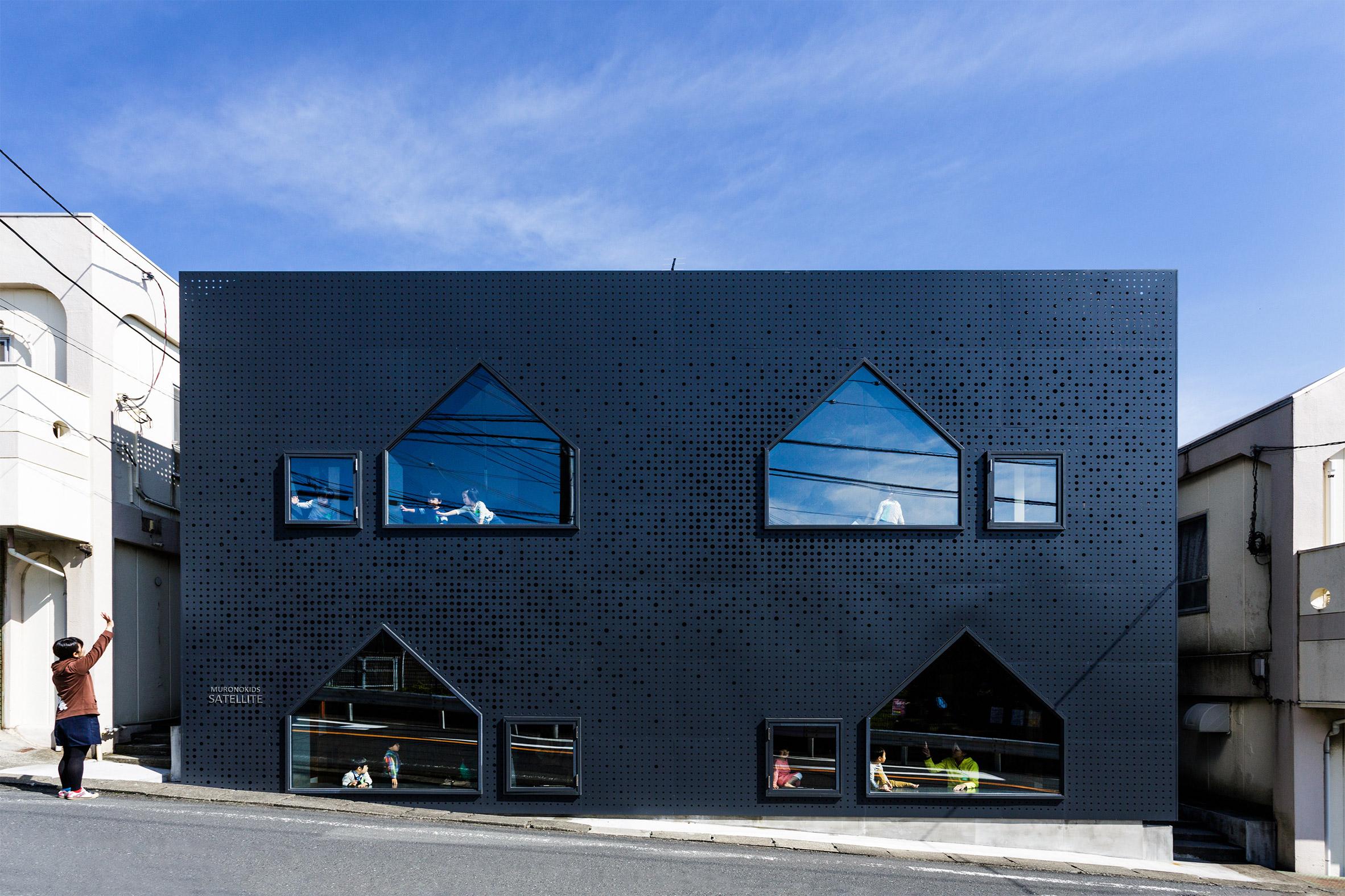 House-shaped windows puncture perforated metal facades of Yokohama nursery