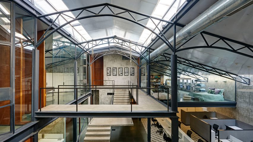 Offices in a converted warehouse centre around suspended concrete staircase