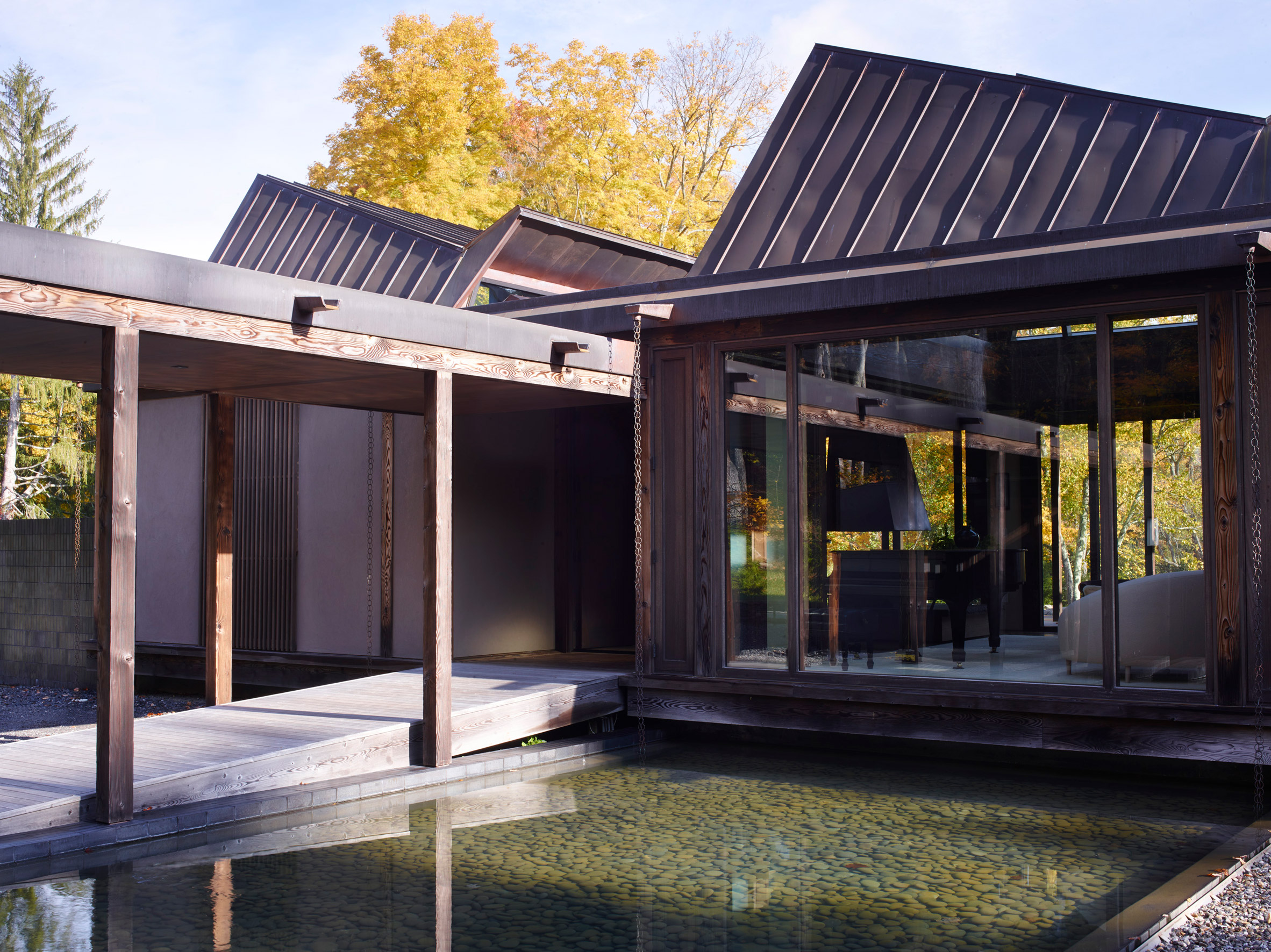 House clad in slate shingles by Telha Clarke features glazed gable end