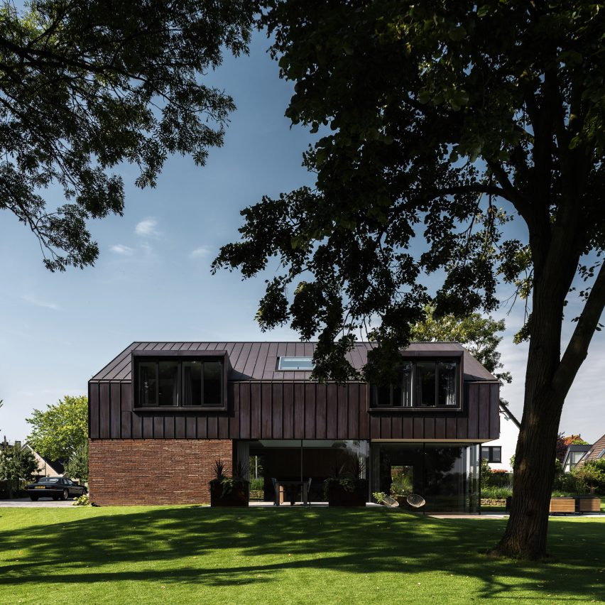 Villa IJsselzig by EVA Architecten is a riverside home featuring red-brick walls and a patinated copper roof