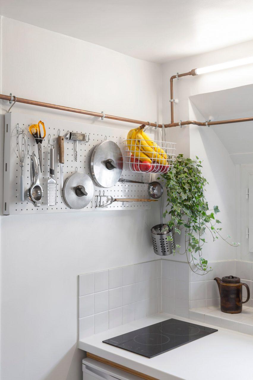 Copper pipes create storage solutions for Paris studio flat