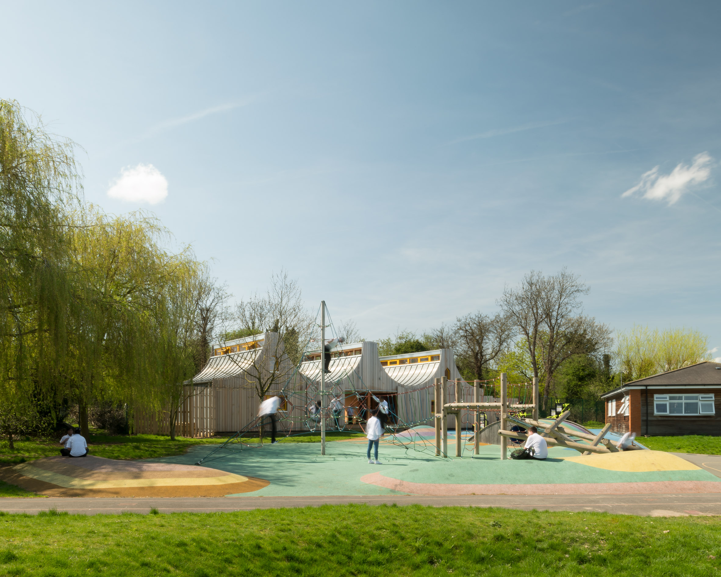 Sliding doors connect school building by Studio Weave to playground and woods