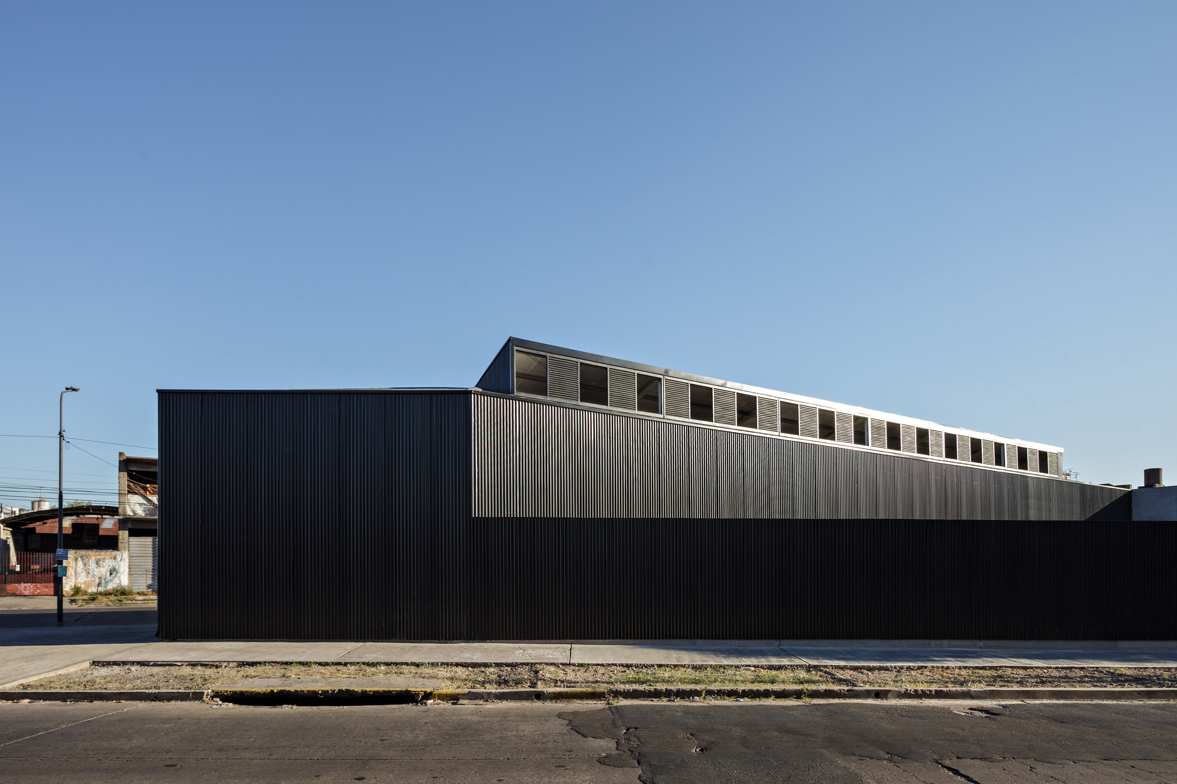 Minimalist black warehouse by Moarqs occupies triangular site outside Buenos Aires