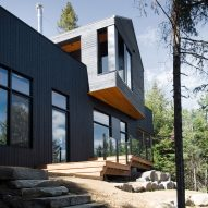 Black Quebec chalet by Atelier Boom-Town overlooks forest and lake