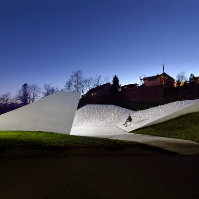 Sloping concrete volumes enclose social hub and chapel in a Slovenian village