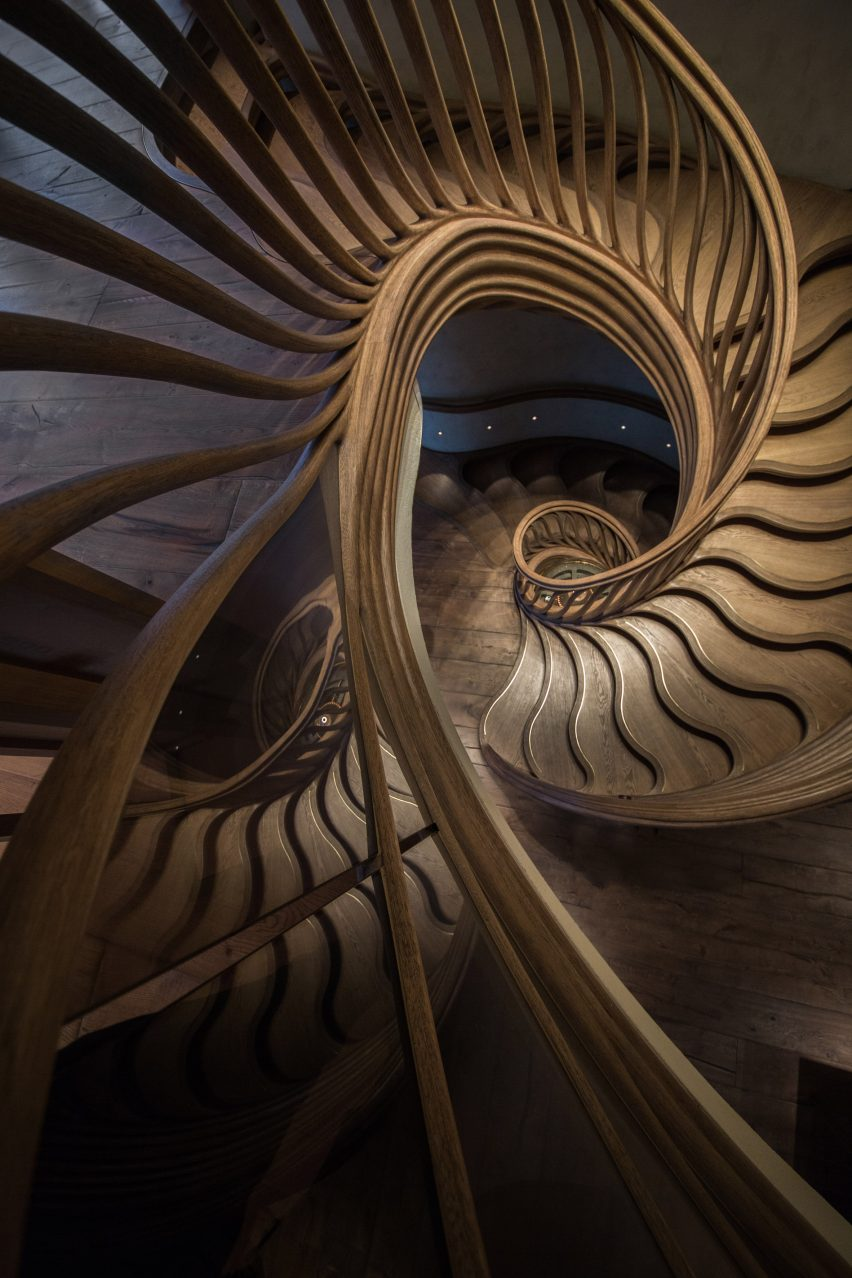 "Atmos Studio's spiralling timber staircase features ""leaf-like"" stairs that emerge from a structural stem"