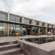 Board-marked concrete walls frame pool views from AT House