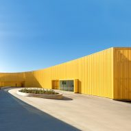 Yellow metal walls wrap Animo South Los Angeles High School by Brooks + Scarpa