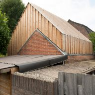 Timber-clad painting studio by Open Kaart wraps around and old brick shed