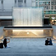 Fountains jet water over entrance to Foster + Partners' sunken Apple Store in Milan