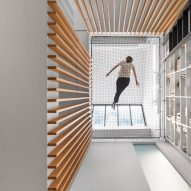 Robitaille Curtis stretches trapeze net across void at Atrium Townhome in Montreal