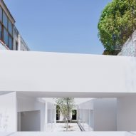 White volumes by HW-Studio form food market between stone buildings in Mexico