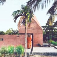 Red concrete meditation space sits under pyramidal roof in rural India