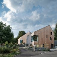 "Arklab creates matching larch-clad houses with ""the same DNA"""