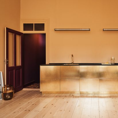 Reform hacks IKEA cabinets to create gold-hued kitchen for designer Stine Goya