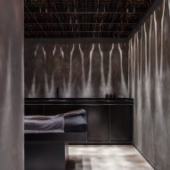 Darkened wood and concrete form moody interiors of Chaps & Co barbershop in Dubai