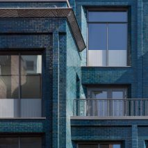 Iridescent turquoise bricks front Damien Hirst's new studio by Stiff + Trevillion