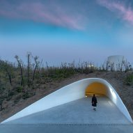 Open Architecture builds cave-like art gallery inside a sand dune