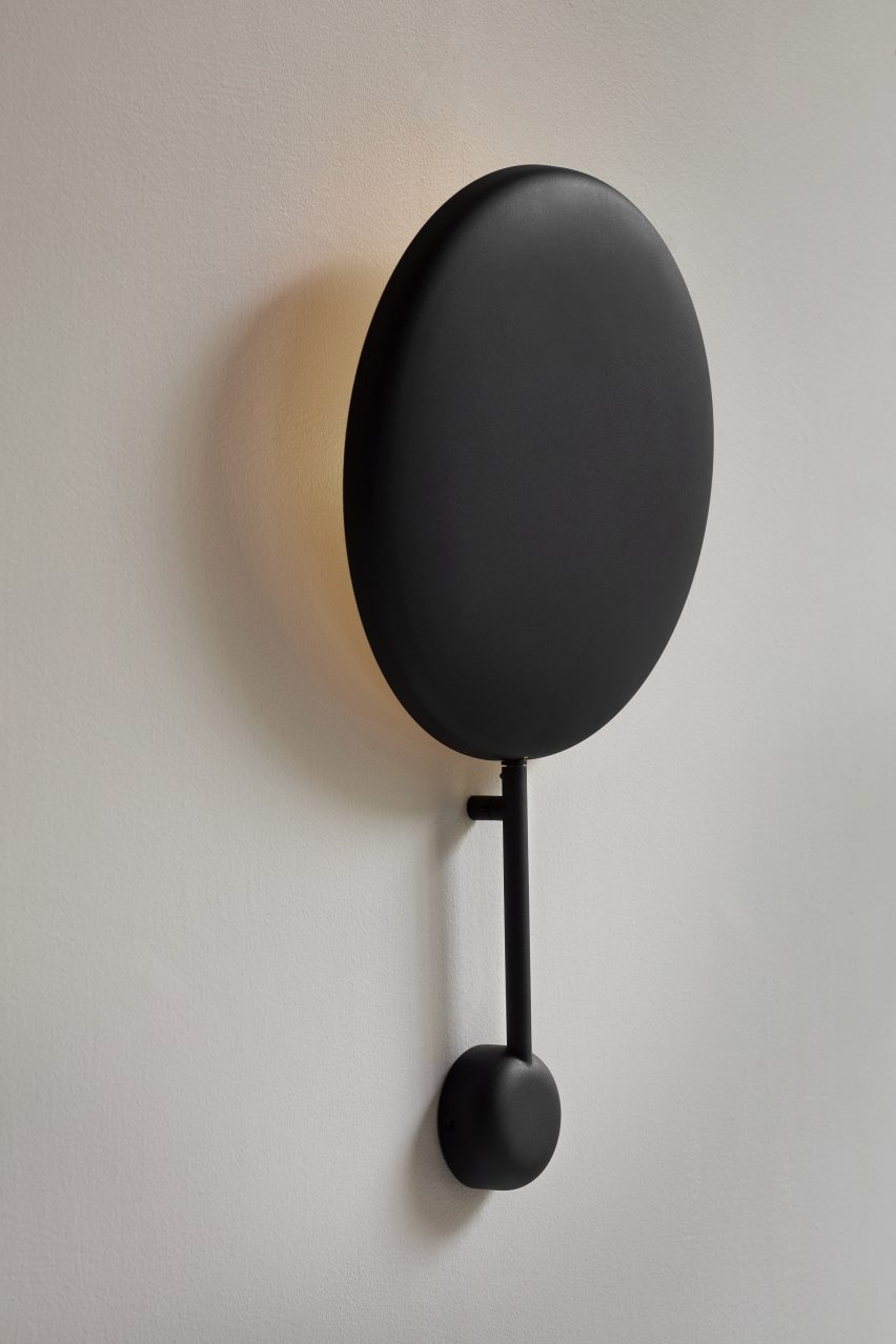 The Ink wall lamp features a concave disc-shaped body with a matt black finish