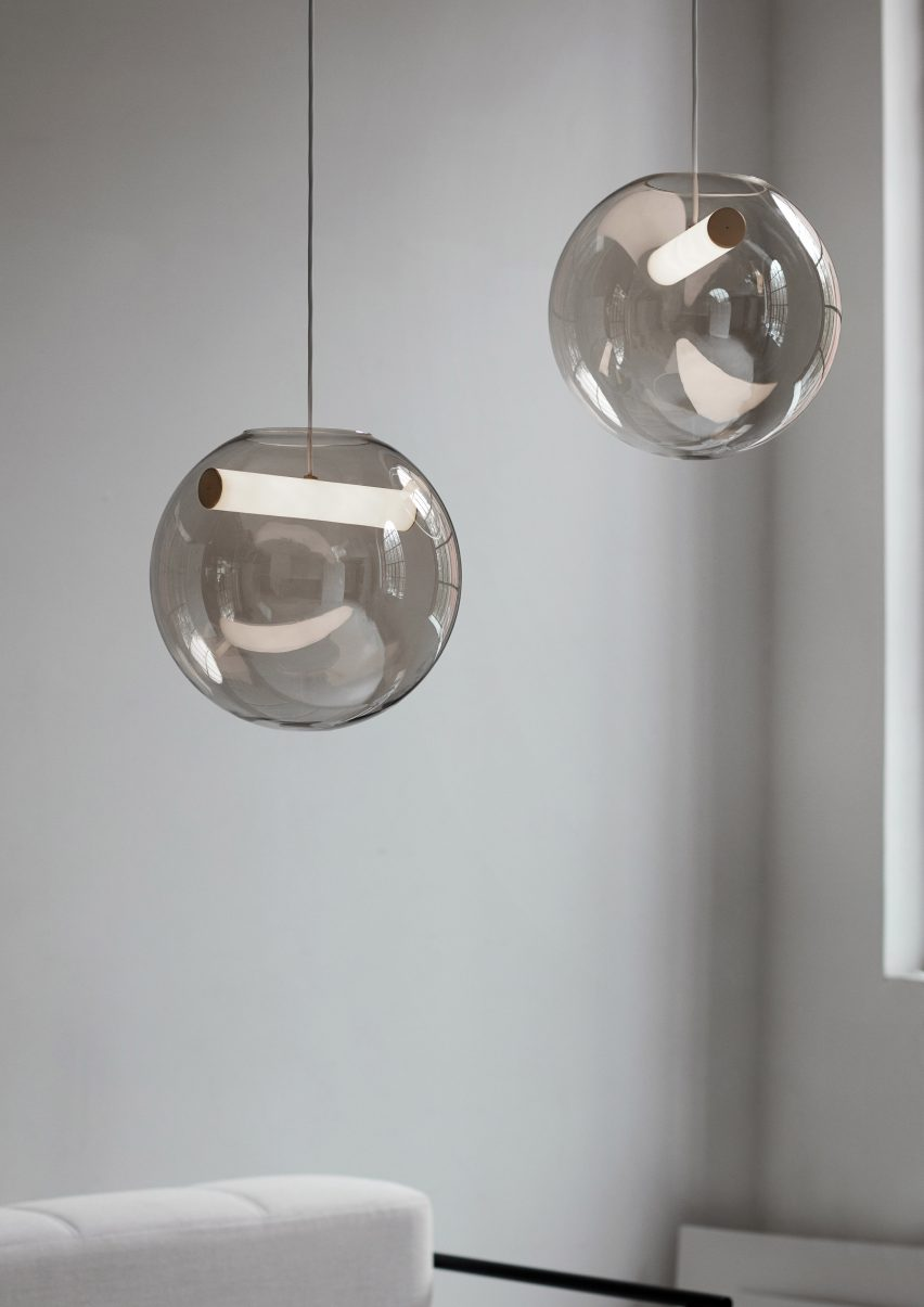 The Reveal pendant lamp by Silje Nesdal comprises a hollow sphere of glass, framing a horizontal light suspended on a copper-coated cord.