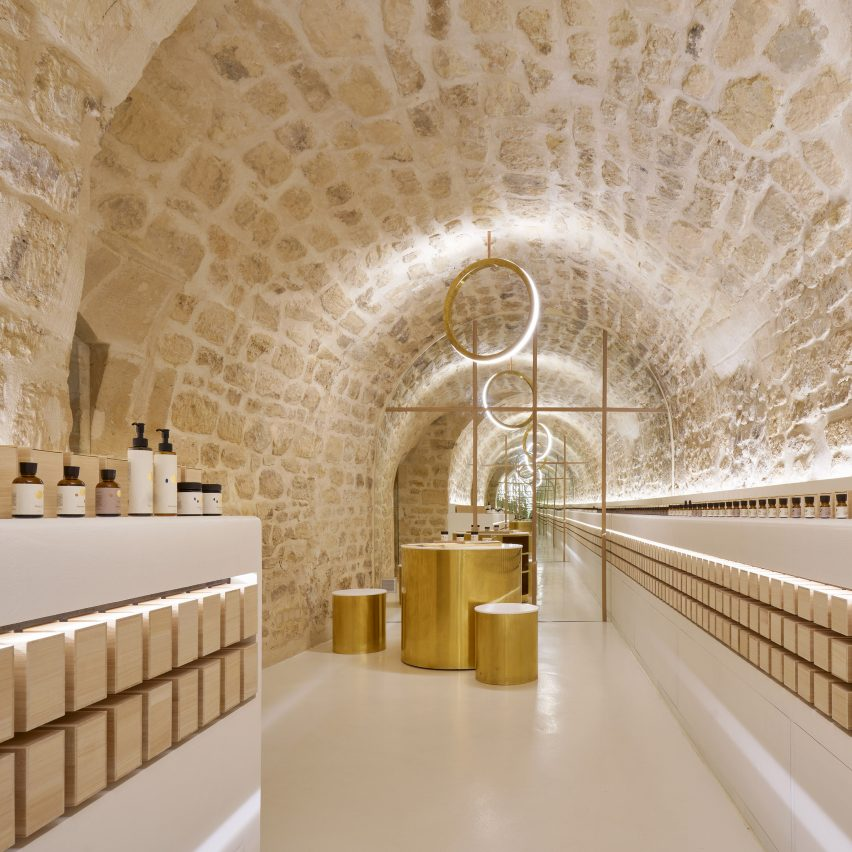 Old stone contrasts with polished brass inside En skincare store in Paris by Archiee