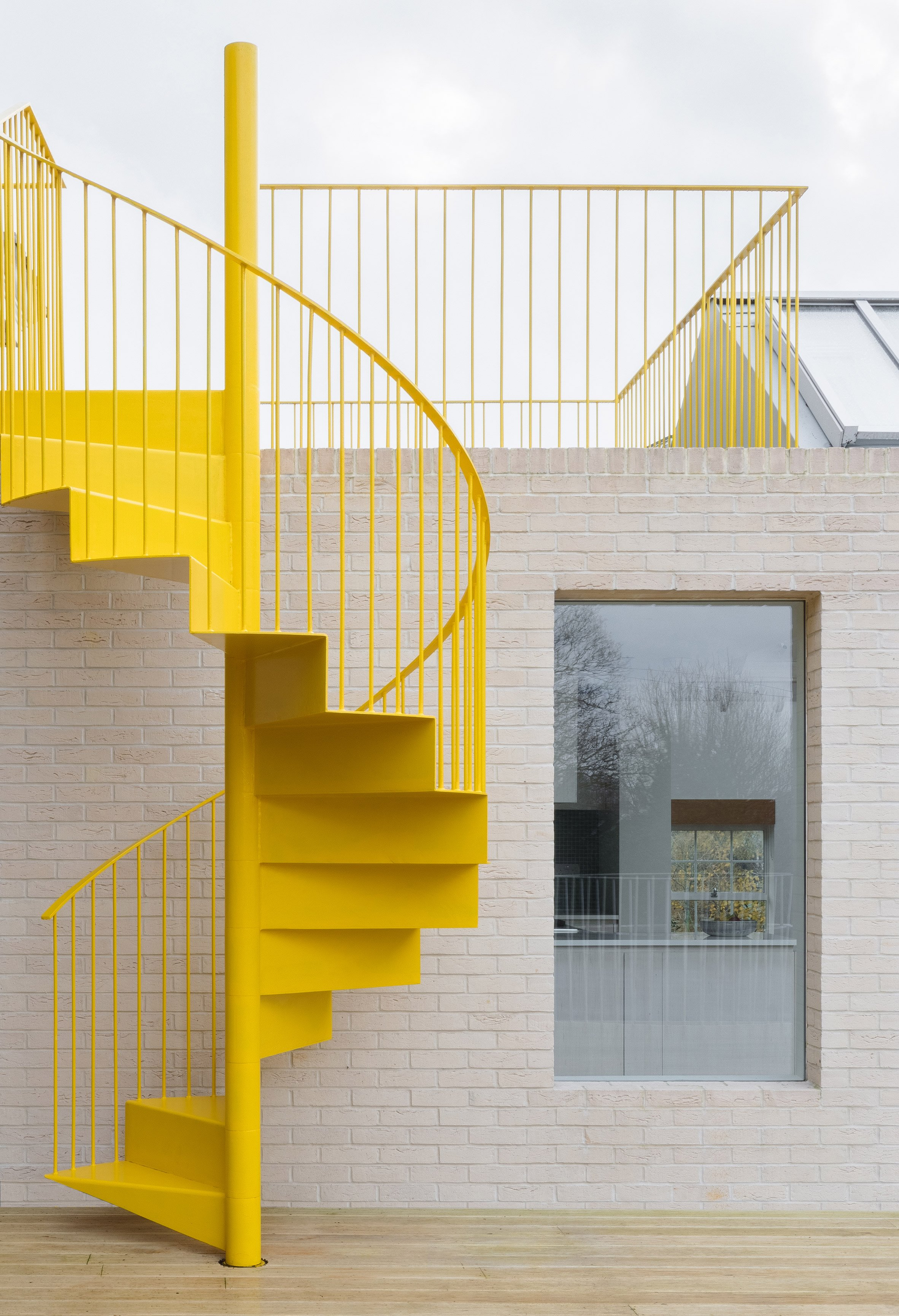 Yellow staircase at Mile End Road apartment by Vine Architecture Studio