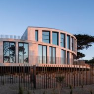 Woods Bagot builds sweeping stone house overlooking the ocean