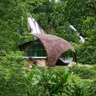 Curved thatched roof covers Chieng Yen Community House in a Vietnamese forest