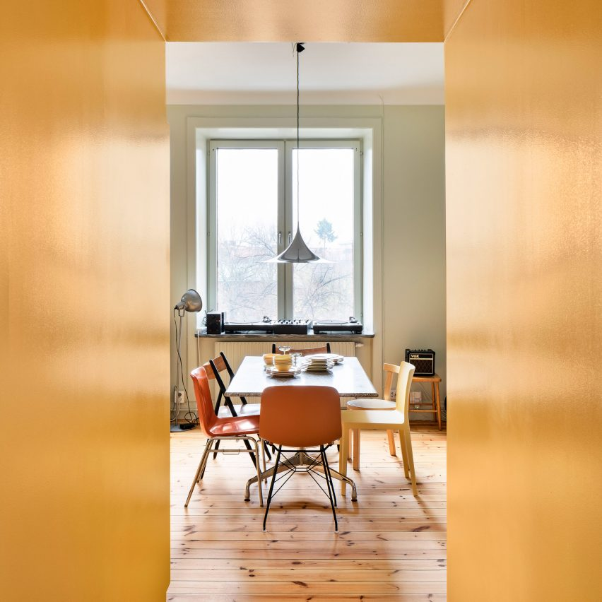 Storage walls define space within bright yellow apartment in Stockholm