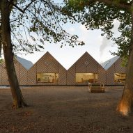 Tracks Architectes designs timber-clad kindergarten with gabled forms in France