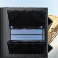 Large mechanical shutters cover windows of Black Box extension by MATA Architects