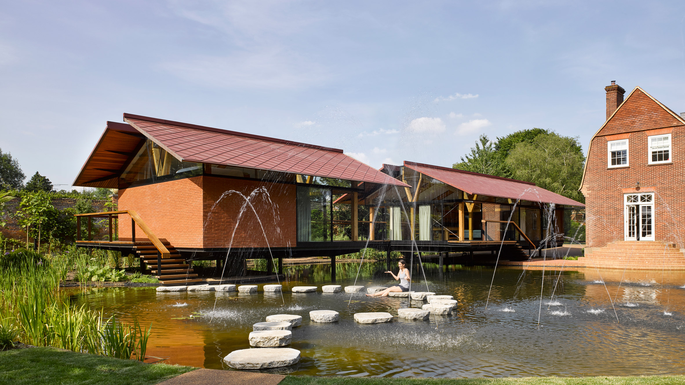 Stepping stones lead into house extension over a lake by