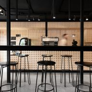 Wooden pegboards wrap walls of Mexico's Negro Blanco Café by Estudio Yeye