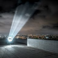 Alex Israel projects Bat Signal from roof of Le Corbusier's Cite Radieuse