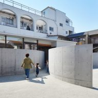 Arced concrete walls invite visitors into House in Konohana