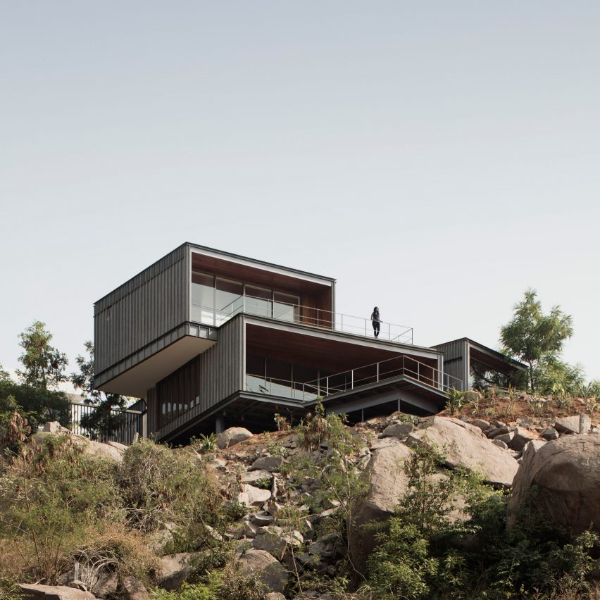 Granite boxes form clifftop house overlooking a lake in India