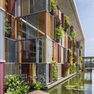 Colourful metal screens and plants cover factory and offices in Hanoi
