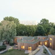 Curving larch wood buildings with green roofs form school extension in Germany