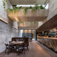 Greenery spills over chunky concrete beams in Lima's Statera Restaurant