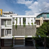 Perforated brick facade shades a house in Vietnam with a triple-height atrium