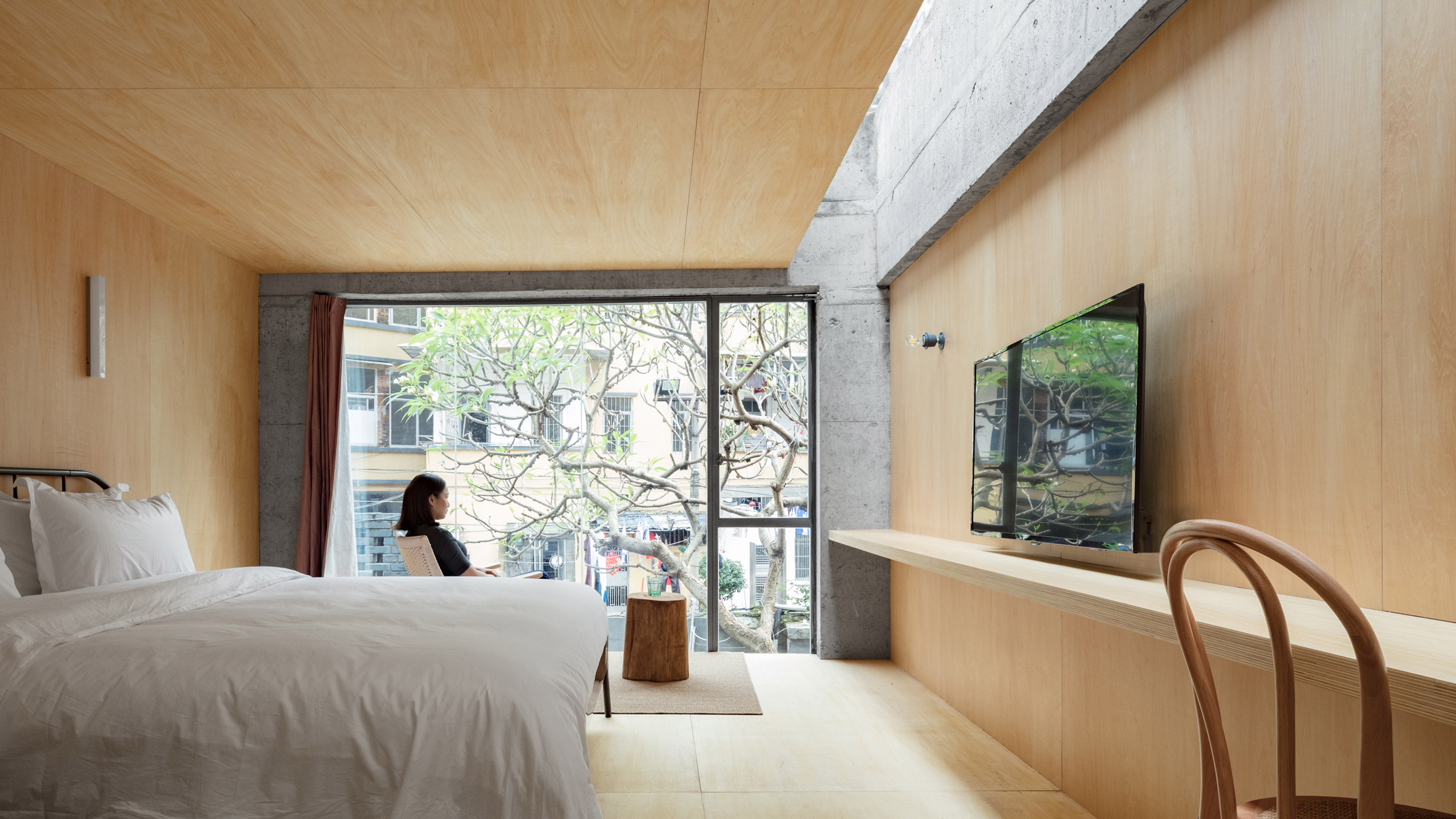 Kooo Architects inserts plywood-lined hotel rooms into an...