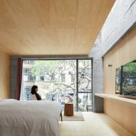 Kooo Architects inserts plywood-lined hotel rooms into an existing concrete frame