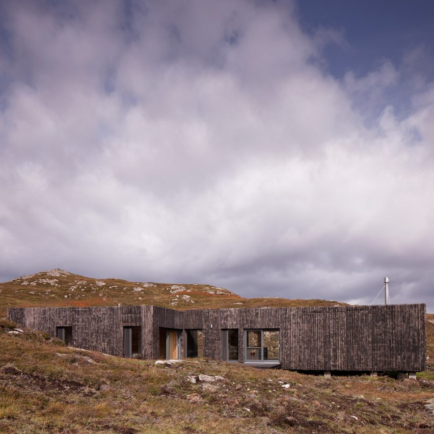 House clad in burnt larch perches on a rocky site in the Scottish Highlands